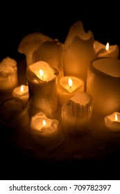 Cluster of new tall candles and melting wax stumps with flames casting yellow light and illuminating the dark scene