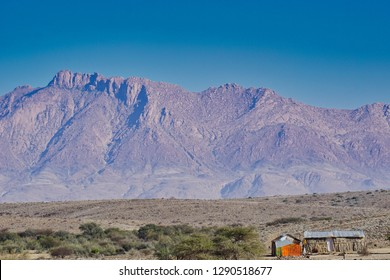 A cluster of ramshackle tin houses at the base of the majestic Brandberg massif. Damaraland, Namibia, Africa.
