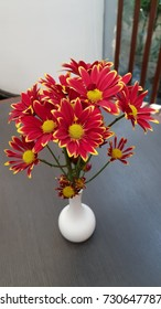 cluster of red flower with yellow pollen , Chrysanthemum, in white jar on the table