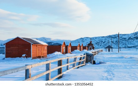 cluster of red Russian residential houses surrouded by deep snow in Teriberka, Russia