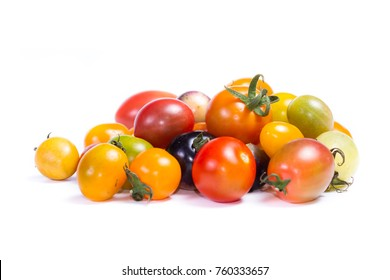 cluster of small cherry tomatoes in a variety of colors isolated on a white background
