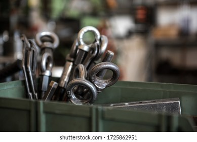 Cluster of steel lifting eyebolts of different dimensions stacked in an army green plastic tray on tool shop workbench