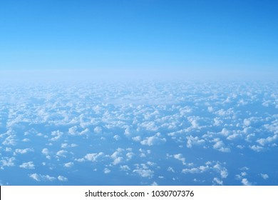 clusters of clouds aerial view with bright sky background, by the window of plane.
