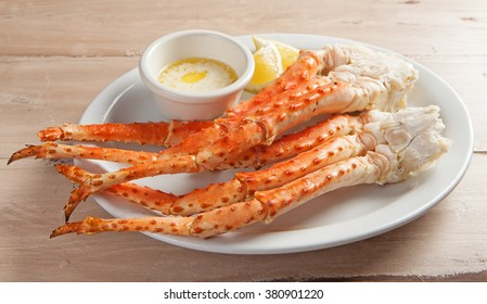 Clusters of fresh snow crab legs on a white plate resting on a wood table with melted butter and lemon