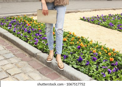 Clutch bag, clutch purse in woman's hands. Woman in light blue jeans and golden leather shoes with handbag walking in the park