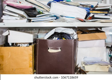 clutter concept - lots of books, papers, boxes on shelf - chaos, order, mess, unorganized