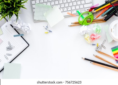 Clutter in office. Desk covered with crumpled paper and scattered stationery. White background top view copyspace