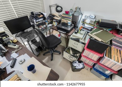 Cluttered messy business office with full file boxes and notebooks.