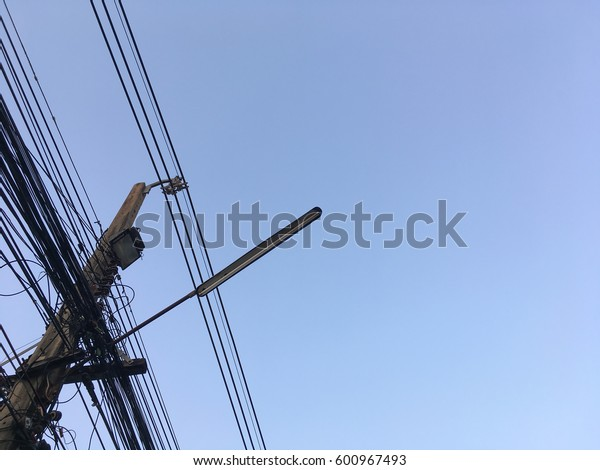 Cluttered power poles wire under the blue sky