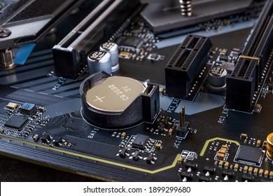 CMOS backup battery for powering BIOS settings and real-time clock circuit on a modern black motherbord. Computer mainboard circuit components. Desktop PC hardware components. Close-up.