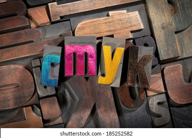 cmyk written with colored vintage letterpress printing blocks on random letters background