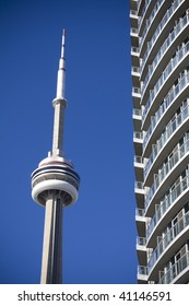 CN Tower beside condominium in toronto against clear blue sky