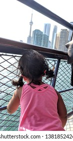 CN Tower, Toronto, Ontario, Canada - June 20th, 2018; Child looking towards the CN Tower Toronto Skyline in a beautiful, clear, bright, Summer Scenic Background from a ship