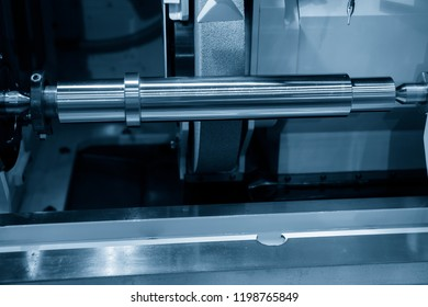 The CNC cylindrical grinding machine making the  shaft part. Automotive part manufacturing process.
