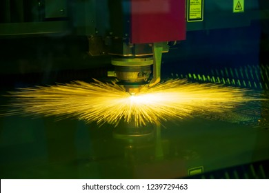 The CNC fiber laser cutting machine cutting the sheet metal plate  with the sparking light. Modern sheet metal manufacturing process.