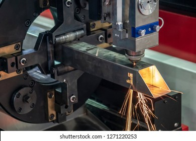 The CNC fiber laser cutting machine cutting the stainless square  pipe or tube  with the sparking light. Modern sheet metal manufacturing process.