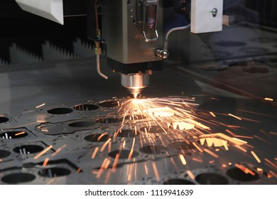 The CNC laser cut machine while cutting the sheet metal with the sparking light