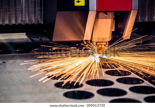 CNC Laserschneiden von Metall, moderne industrielle Technologie. Kleine Feldtiefe. Warnung - Authentisches Schießen unter anspruchsvollen Bedingungen. Ein bisschen Korn und vielleicht unscharf.