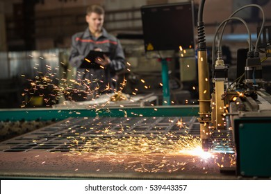 CNC Laser Plasma. Selective focus on laser plasma cutting of metal modern technology in process at metalworking manufacturing plant male worker on the background copyspace