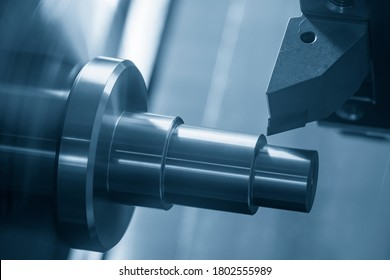 The  CNC lathe machine cutting the metal shaft parts. The hi-technology metal working processing by CNC turning machine .