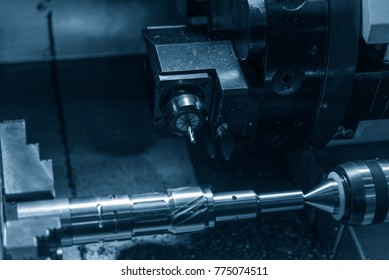 The CNC lathe machine cutting the steel shaft. The slot cutting process on the metal shaft with the turn-mill machine.