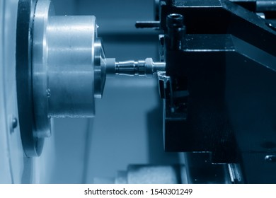 The CNC lathe machine in metal working process cutting the screw and nut parts with the cutting tools. The automotive parts production processing by CNC turning machine .