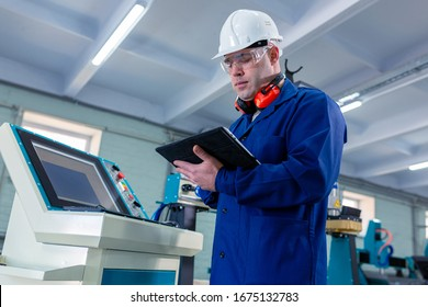 CNC machine operator in the Hard  white Hat Walks Through Light Modern Factory While Holding tablet. Successful, Handsome Man in Modern Industrial Environment.