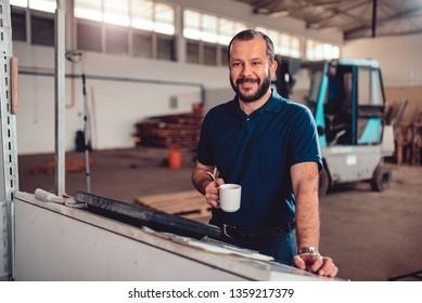 CNC Machine Operator wearing blue shirt having coffee brake in industrial factory