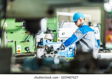 CNC Metal Lathe Technician Worker. Caucasian Contractor Operating Heavy Duty Metalworking Machinery.