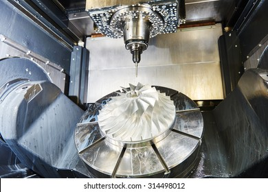 cnc metal working machining center with cutter tool during metal detail milling at factory. Authentic shooting in challenging conditions. Maybe little blurred.
