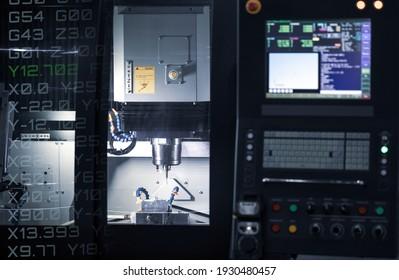 CNC milling machine cutting automotive part. CNC programming code. Industrial manufacturing metalwork