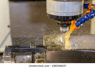 The CNC milling machine cutting the mould parts with indexable tool. The oil coolant method in CNC milling process.