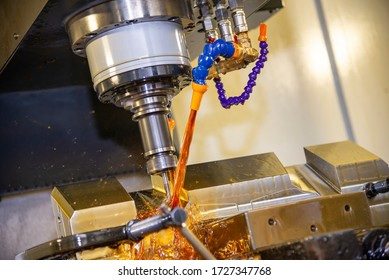The CNC milling machine cutting the tire mold parts with liquid oil coolant method. The mold and die manufacturing process by CNC machining center.