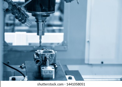 The CNC milling machine drilling the hole at the automotive parts.The automotive parts manufacturing process by machining center.