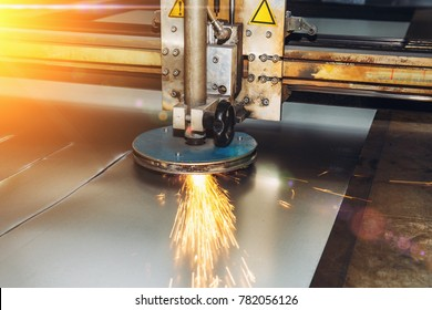 CNC programmable laser plasma cutting machine cuts sheet of metal with sparks, modern industrial metalwork technology, professional manufacturing equipment