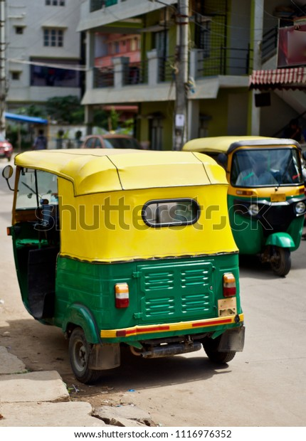 A CNG auto rickshaw is running on an Indian road isolated unique photograph