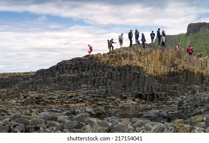 CO. ANTRIM, NORTHERN IRELAND - JUNE 28 - A group of tourists exploring the Giant's Causeway in the Summer of 2014.