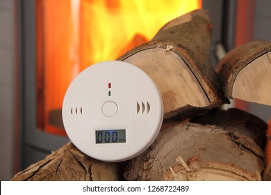 a CO detector in front of a burning fireplace