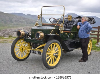 CO. KERRY, IRELAND - JULY 11 2006: A senior man, proud owner of an elegant vintage car from the Edwardian era, stands beside his vehicle in a roadside car park in the Kerry mountains.