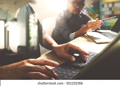 Co worker process, entrepreneur team working in creative office space. using digital tablet docking keyboard and laptop with smart phone on marble desk,light beam effect