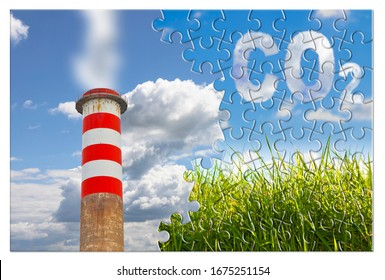 CO2 concept image in jigsaw puzzle shape against a green wild grass on sky background and an high concrete chimney emits fumes.