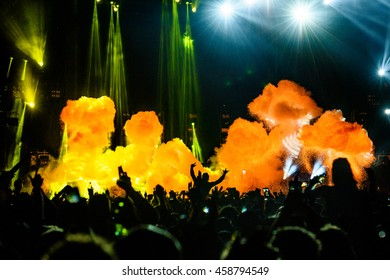 Co2 and Fire Silhouette Concert People on Shoulders in Crowd with hands up at a Music Festival - Backlit with Lighting.