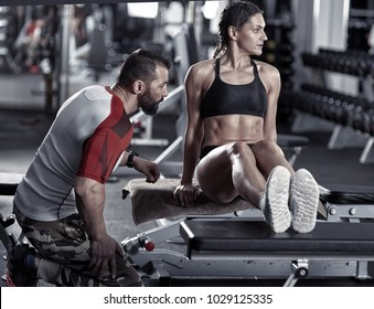 Coach assisting woman with triceps dips on bench