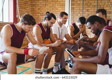 Coach and basketball players using digital tablet in the court