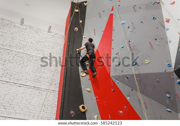 Coach climber belay amateur athlete on a high climbing wall.