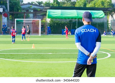 Coach is coaching Children Training In Soccer Team