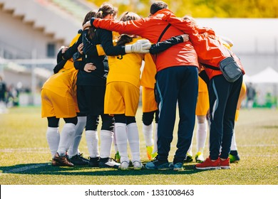 Coach coaching Girls Sports Team. Girls school sports team huddling with coach on the grass field. Soccer football junior girls team at sports outdoor field before match. Coach Building Confidence