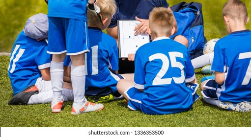 Coach Coaching Kids Soccer Team. Youth Football Team with Coach at the Soccer Stadium. Boys Listening to Coach's Instructions Before Competition. Coach Giving Team Talk Using Soccer Tactics Board
