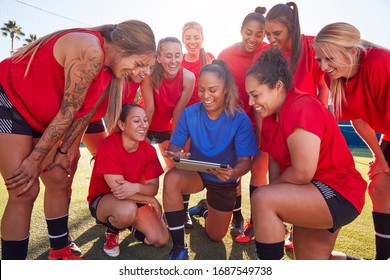 Coach With Digital Tablet Discussing Tactics With Womens Football Team Training For Soccer Match