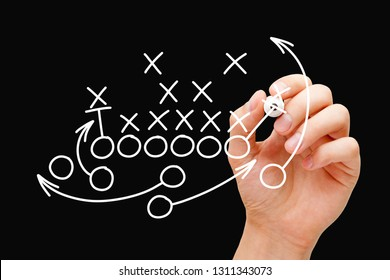 Coach drawing american football or rugby game plan, strategy and tactics with white marker on transparent wipe board.